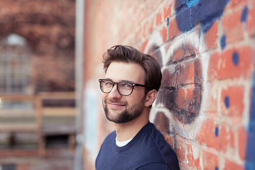 Portrait of Smiling Young Man with Facial Hair Wearing Eyeglasses and Leaning Against Brick Wall Painted with Graffiti-1