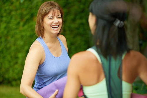 Two mature women talking before doing yoga in the summer-1