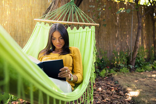 Woman lying on hammok and reading book outdoors